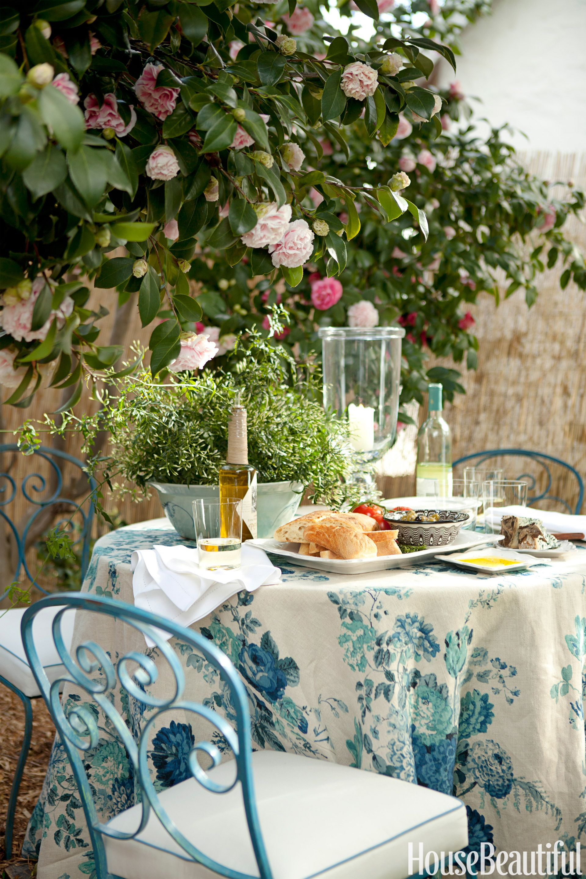 Camellias arch over an outdoor dining table draped with a clarence house linen dahlia crisp hemstitch linen napkins candlelight