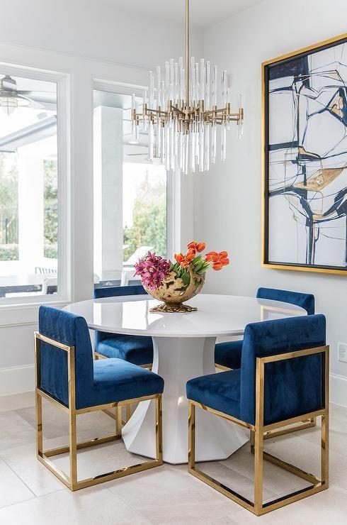 ein runder wei er esstisch mit goldenen und blauen saphir st hlen unter einem messing und. Black Bedroom Furniture Sets. Home Design Ideas
