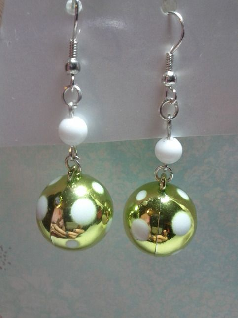These adorable earrings are handmade by me. They each feature a round green bead with white spots and a small white round bead.