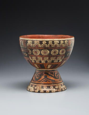 Aztec, Eastern Nahua, Polychrome Goblet, ca. A.D. 1300-1521 Earthenware with polychrome paint height 7in (17.1cm) Finely executed complex design with smoke or mist scrolls surrounding the base surmounted by a black and orange greca frieze. The cup itself features black, white and red banded textiles surmounted by alternating bands of cut shell ornaments with maize ears alternating around the rim.
