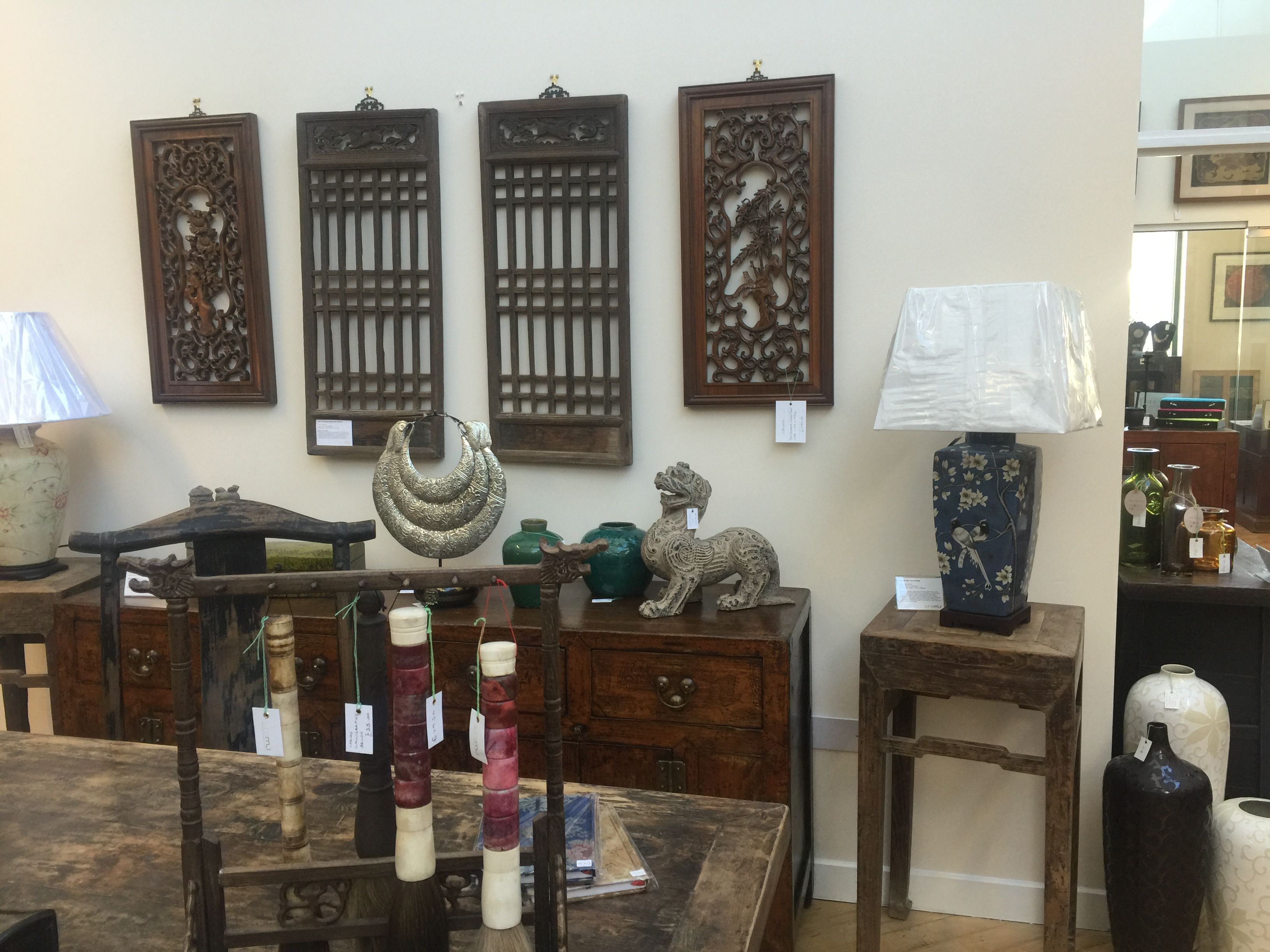 Bold carved wooden wall panels over an antique sideboard the