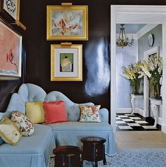 The paintings framed in gold, the idea of a corner banquette (but not this one), the stools, and the wonderful ram's head console tables through the doorway = wow!