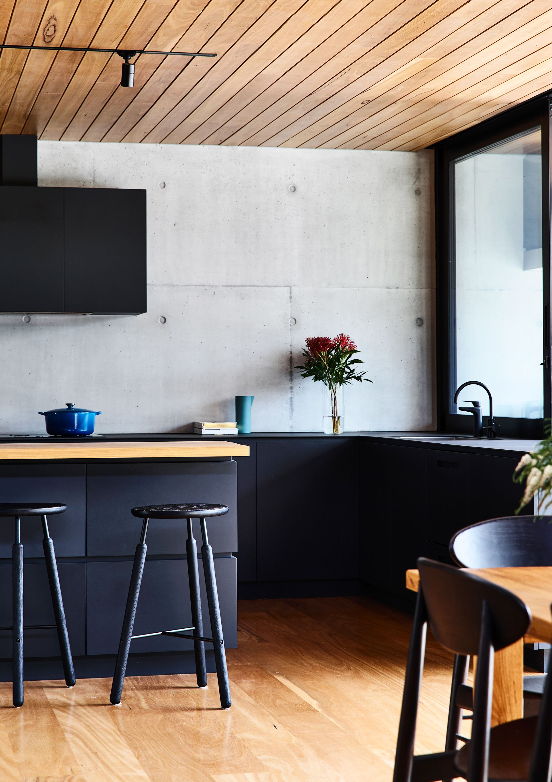 Timber benches are paired with sleek black cabinetry and a raw