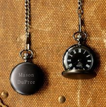 Black metal pocket watch is engraved with a special message.