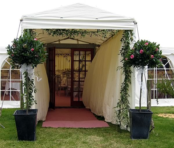 Wedding Altar Hire Uk: Decorated Topiary Framing The Entrance To A Marquee
