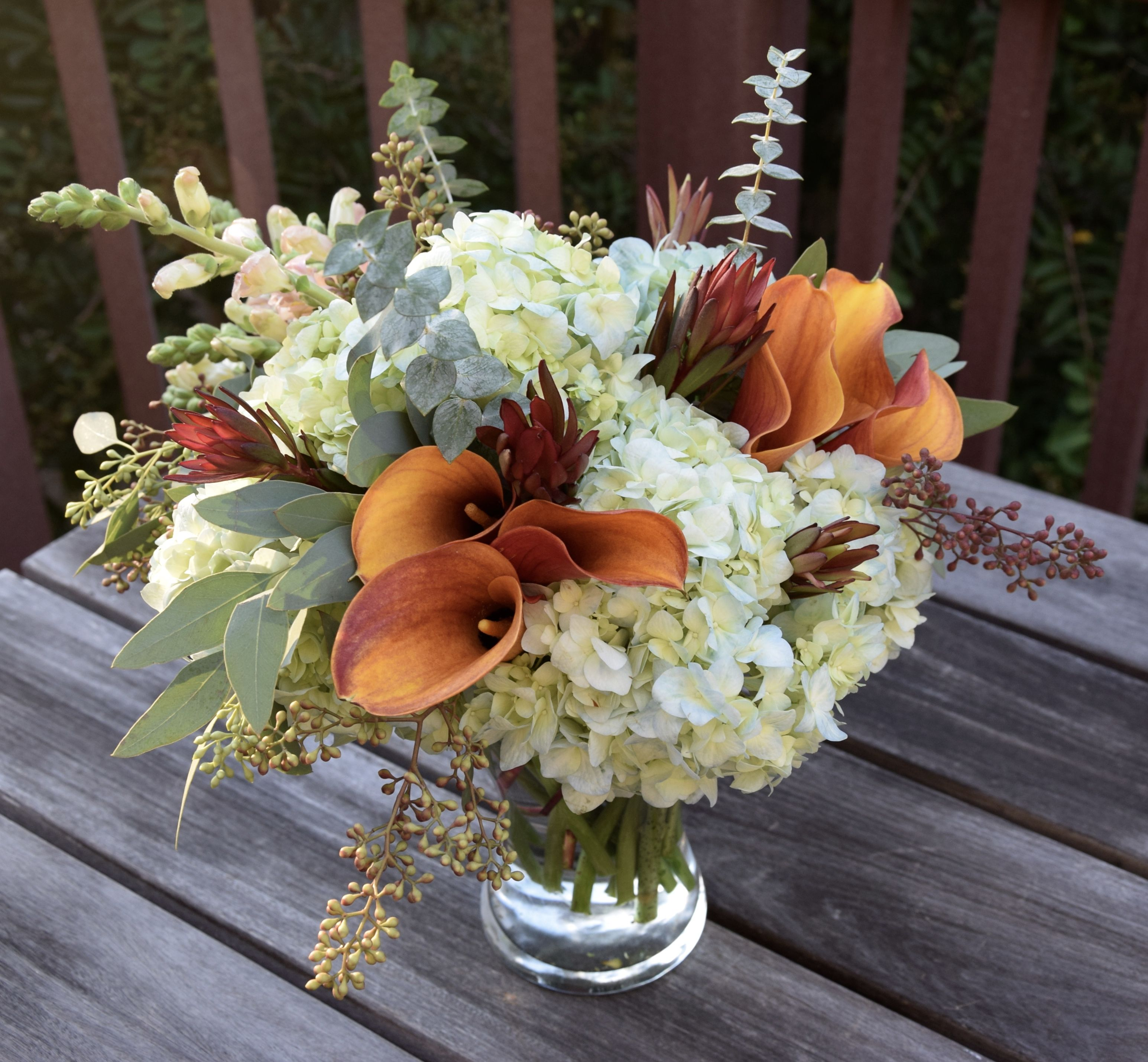 Flower arrangement with burning orange calla lilies and