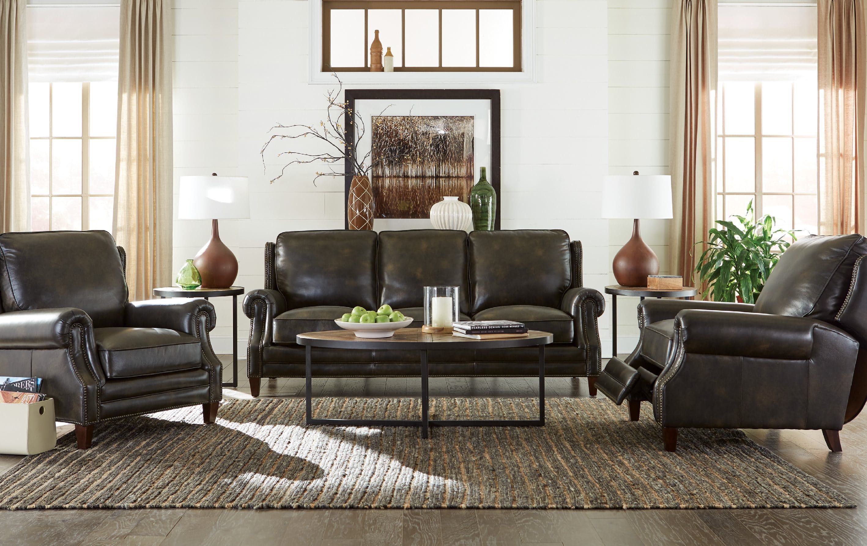 Old world leather with a hand-rubbed effect is the perfect complement to this classically trained design.   It features attached box border backs, traditional rolled arms, tapered wood legs, and brass nail head trim around the base, arms, and wings.