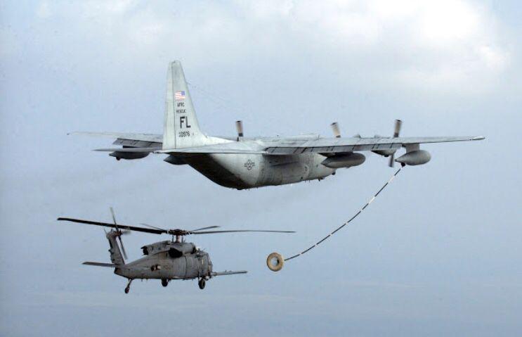 A Lockheed C-130 Hercules refuels a UH-60 Blackhawk.