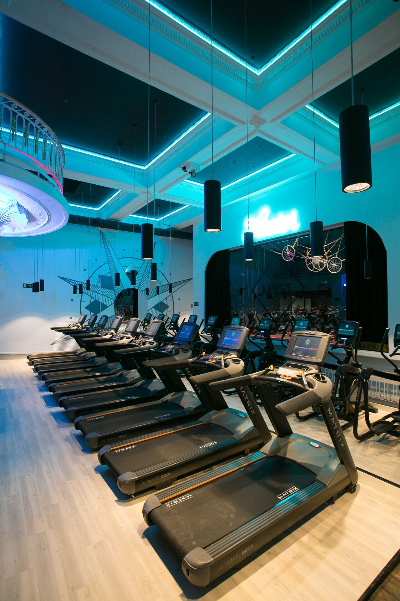 The Myst Gym Club in Madrid looks like a night club: flashy neon lights, resistant floor and people gathered to sweat together! #gerflor #sports #creation #signature #vinyl #floor #gym #madrid #blue #treadmills