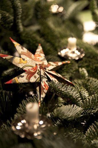 Handgjorda pappersstjärnor och julgransljushållare i plåt pryder denna bordsdekoration