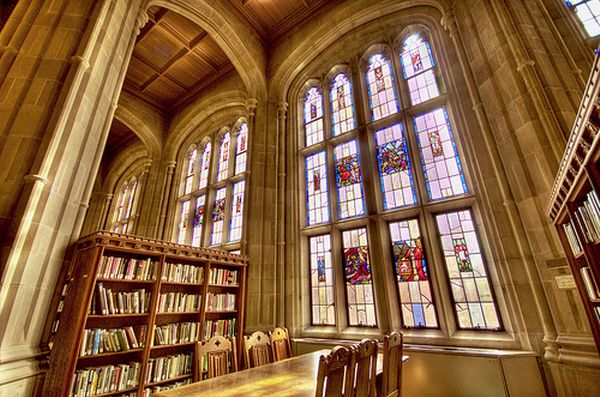 Harvard Divinity Library. Stone arches, bookcases, stained glass windows.