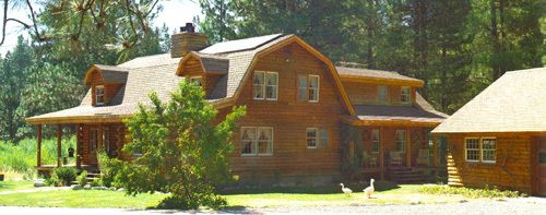 Log home with covered porch and gambrel roof garages for Log cabin roof design