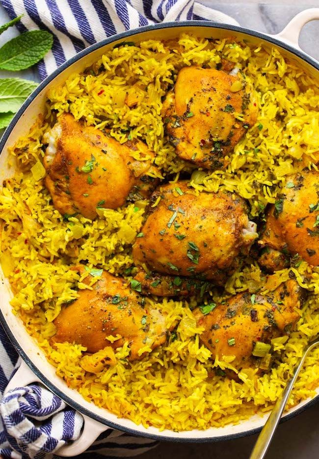 Make this Herby Golden Baked Chicken and Rice - all prepped and cooked in one pot for easy clean up and a satisfying dinner! Juicy chicken thighs are coated in a simple spice blend of cumin, ginger and turmeric and then cooked over golden-seasoned bed of rice topped with loads of fresh herbs. | #GlutenFreeDinner #GlutenFreeRecipes + #DairyFreeDinner #ChickenDinner #HealthyChicken #ChickenandRice #DairyFreeChicken