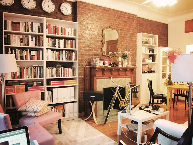 New York Apartment. Ikea White Billy Bookcases, Exposed Brick Wall,  Fireplace, White Ikea Lack Coffee Table. Bike Parked In The Living Room.