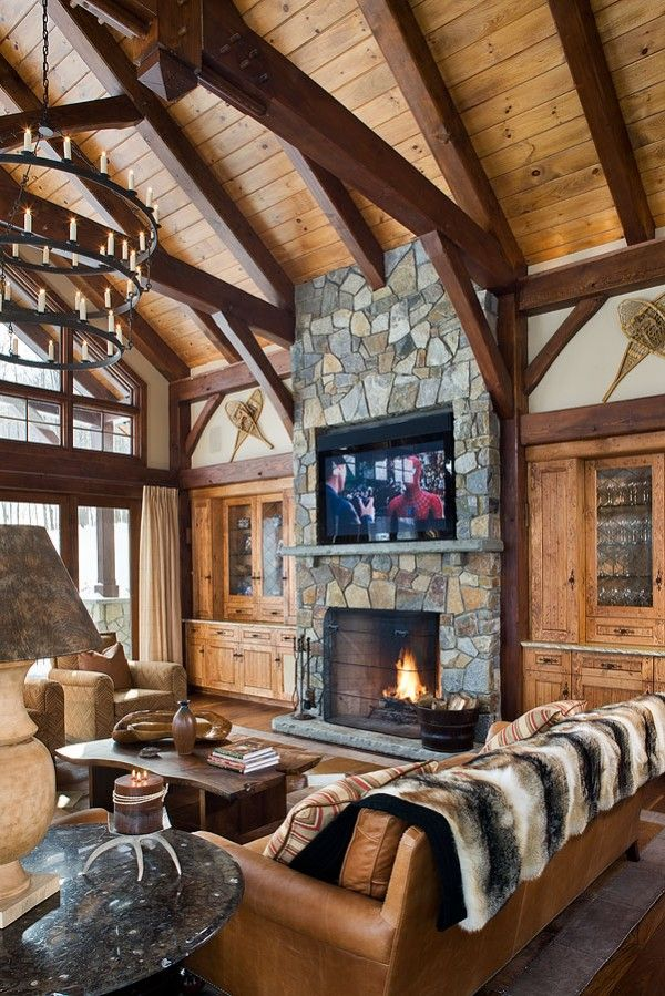 Grand Fireplace W Vaulted Ceilings Beams Open Floor: Great Room With A Large Flat Screen Tv Above The Fireplace