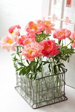 A very adorable way to display flowers: A vintage metal basket holding clear glass bottles.