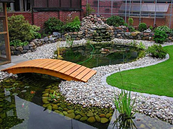 Garden pond We love the wooden bridge waterfeature pond