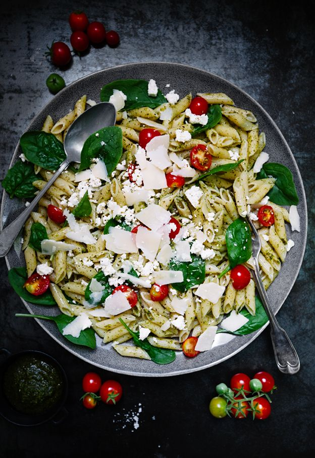 Pasta with homemade pesto, feta cheese, fresh spinach and home grown cherry tomatoes and freshly grated Parmesan cheese.