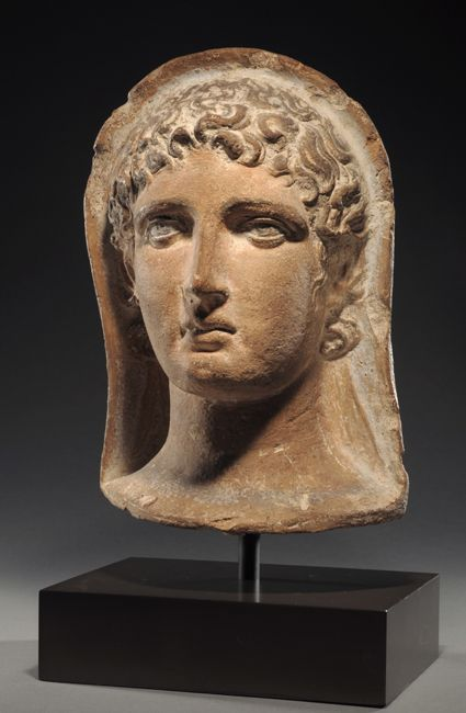Etruscan polychrome terracotta votive head of a young man, 4th century B.C. 26 cm high. Private collection