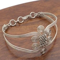 Silverplated copper wire bracelet with woven center surrounded by swirls      Handmade hook and eye closure      15 young men and women find a sustainable income and a path out of the     Nairobi slums by making this jewelry      Bracelet is about 8 inches in length        Working with Jedando Modern Handicrafts the young men and women of Zakale Jewelry produce handmade jewelry using the skills of wir