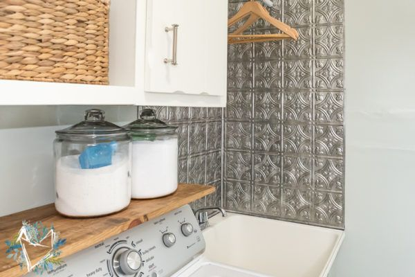 Laundry room utility sink with faux tin backsplash. See 5 laundry rooms that will make you want to wash clothes on DuctTapeAndDenim.com