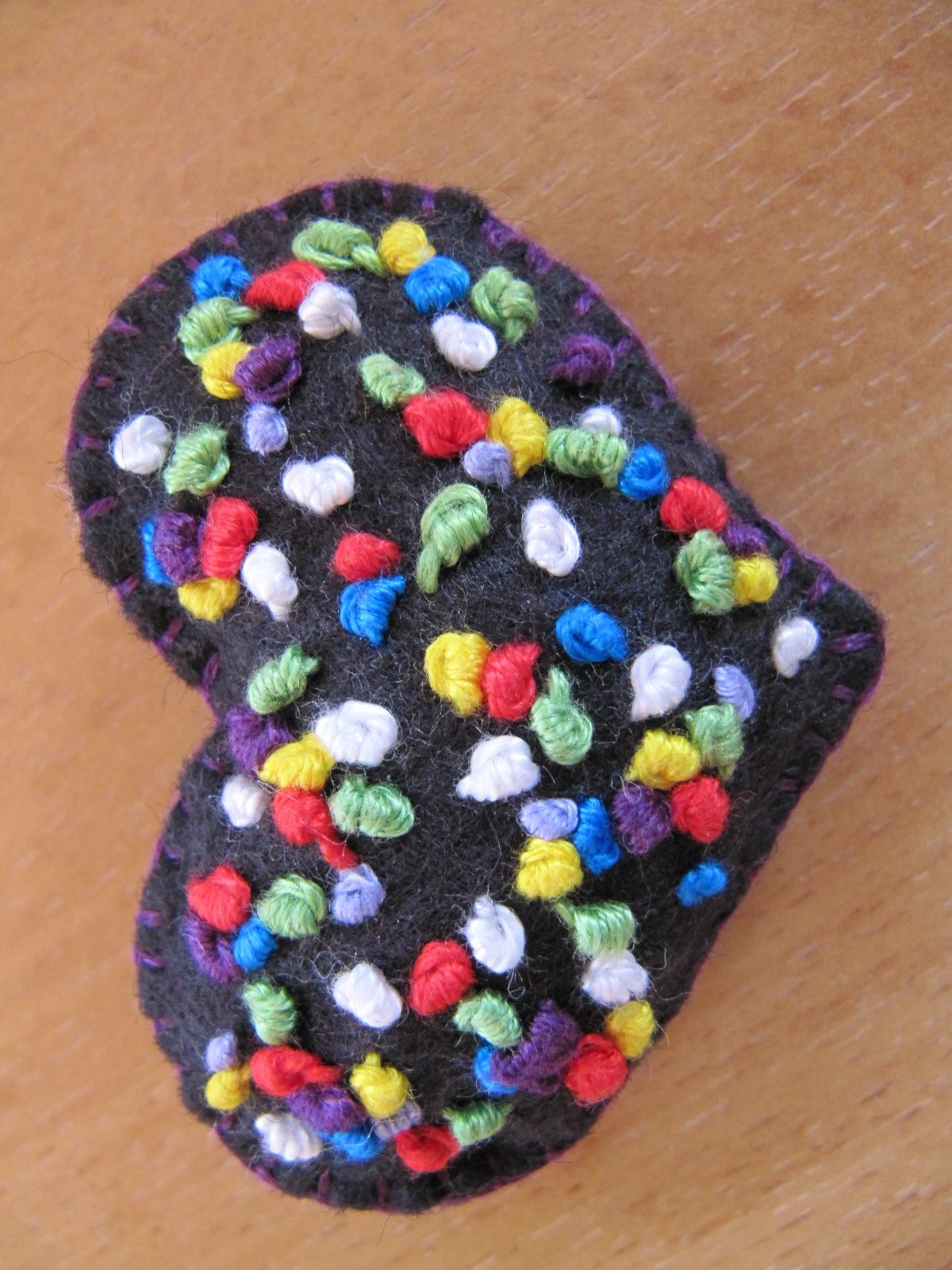 Little handmade padded black felt brooch with hand stitched French knots using vintage threads.
