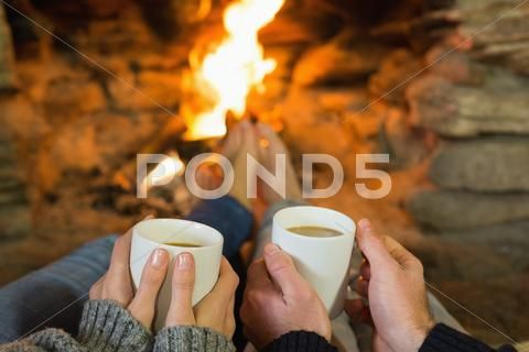 Hands holding coffee cups in front of lit fireplace Stock Photos #AD ,#coffee#cups#Hands#holding