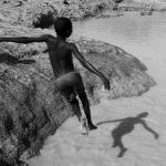 MALI. Dogon region. Sevare. Children playing in the water with goat. 2009.