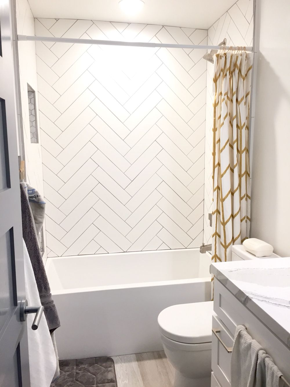 Guest shower. Herringbone white subway tile gray grout. Gold accent ...