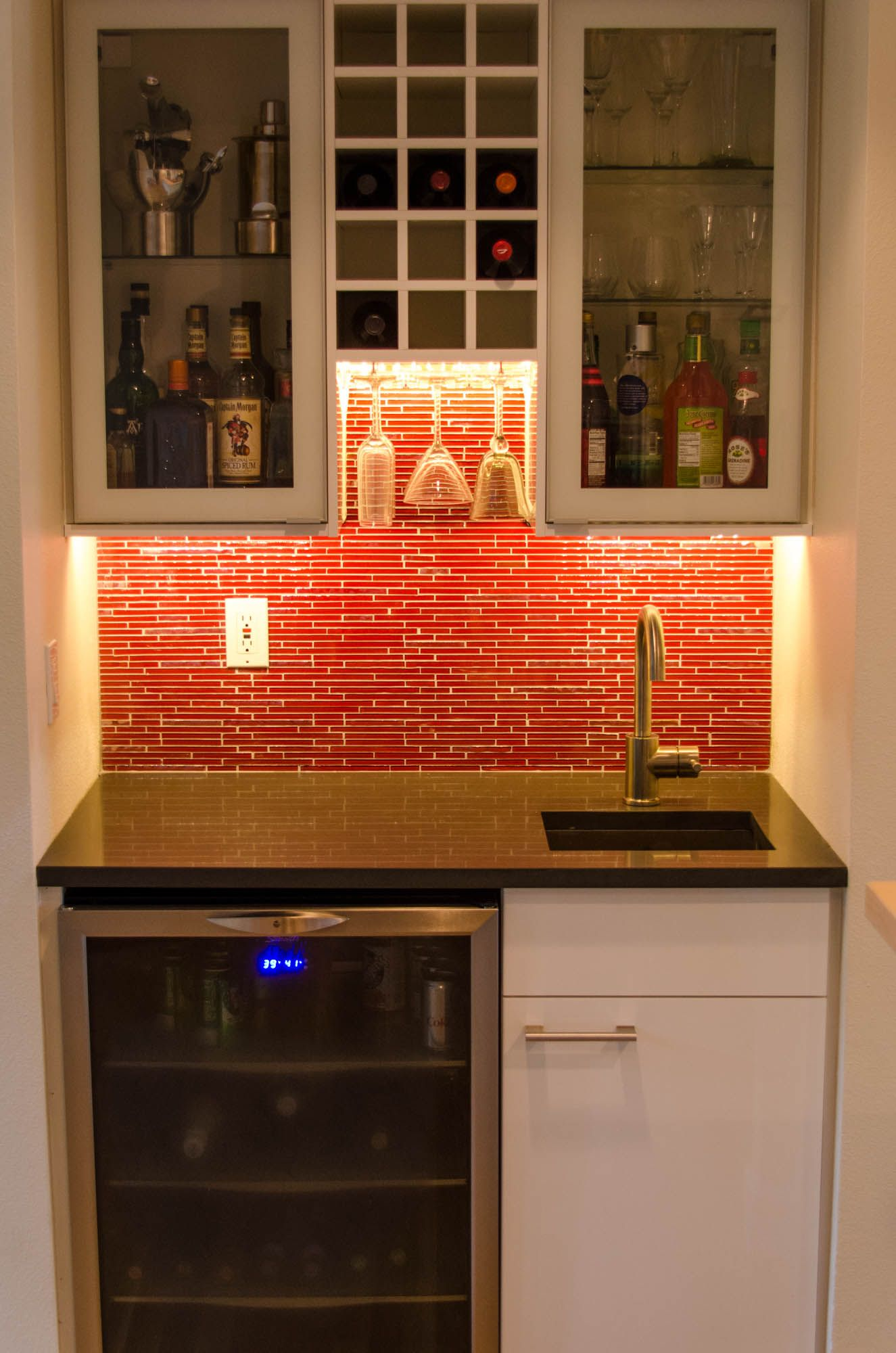Simple wet bar design with glass cabinetry, wine rack and stem ...