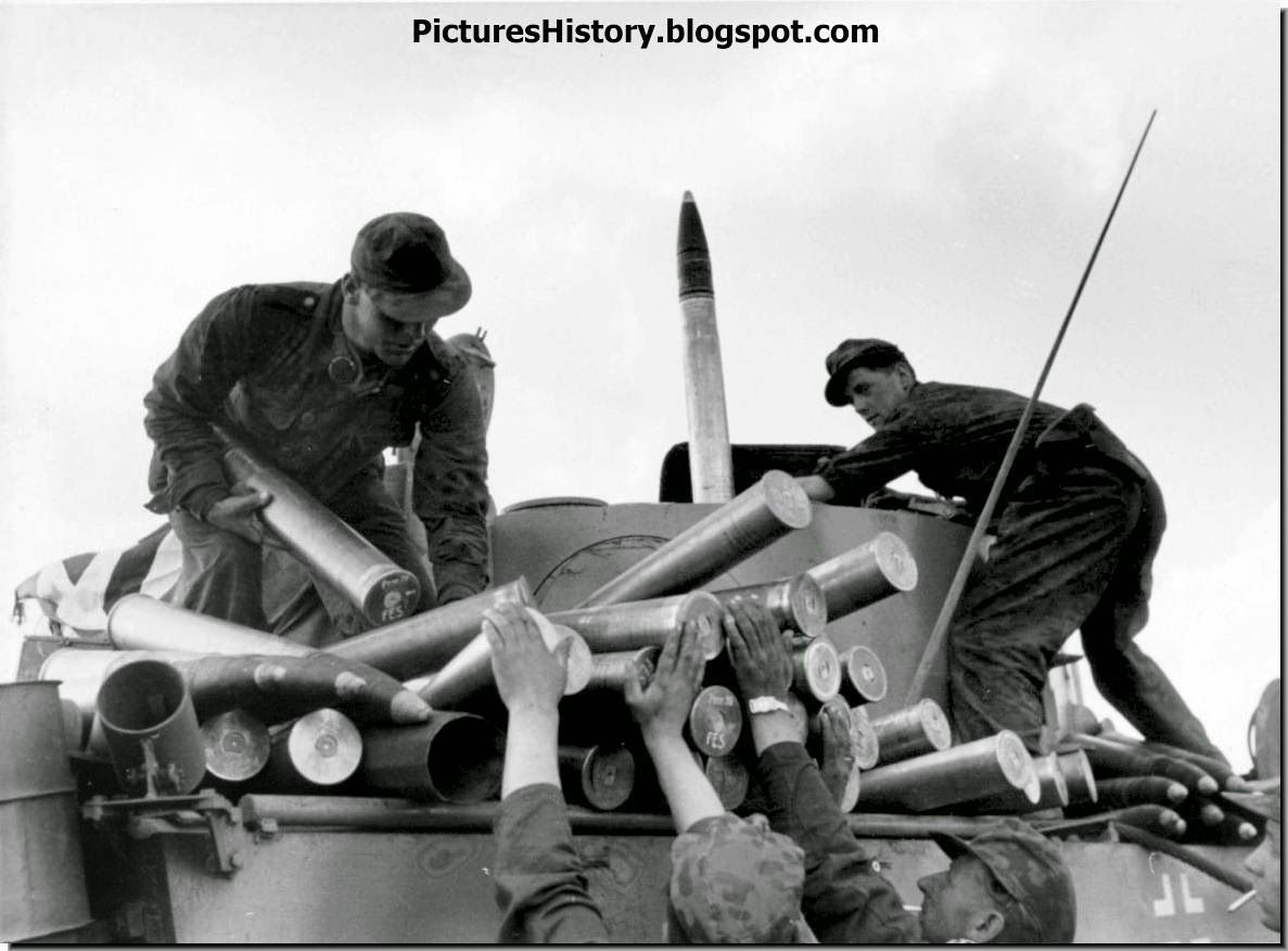 Men from the 5th SS 'Wiking' Division frantically load 88 mm armor piercing shells onto a Tiger tank during the Batle of Kursk. July 1943.