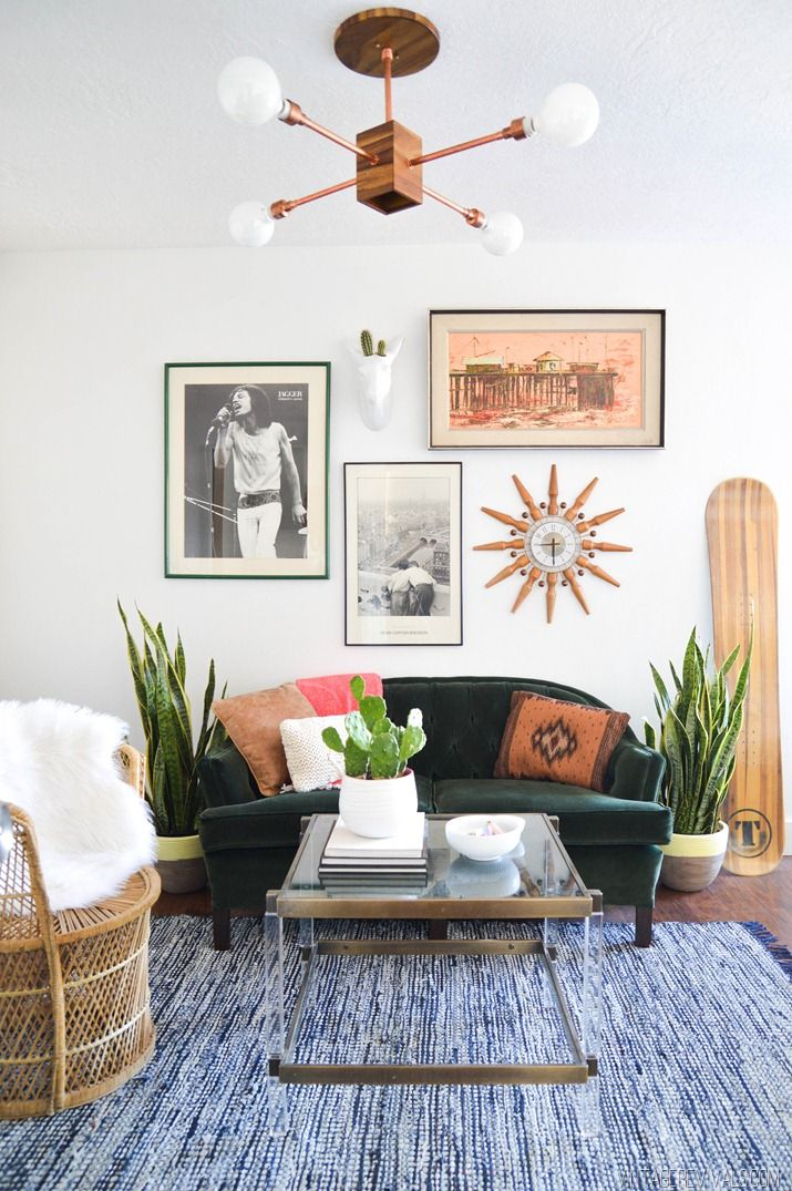 190f57973478 White walls, brown light fixture, green couch, blue rug, glass coffee table