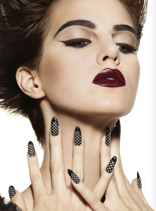 Gorgeous winged eyeliner, heavy brow, dark bold lip with checkered nails.