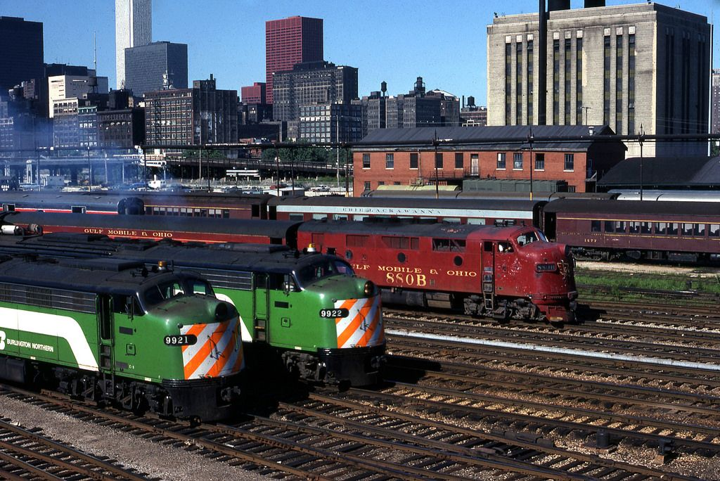 """Caption: """"The Plug by a nose"""" Gulf Mobile & Ohio commuter train (The Plug) and Burlington Northern commuter trains Chicago July 1978 Photo by Bill Raia"""