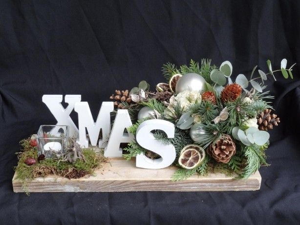 Kerststuk xmas op een steigerhouten plank met de letters van