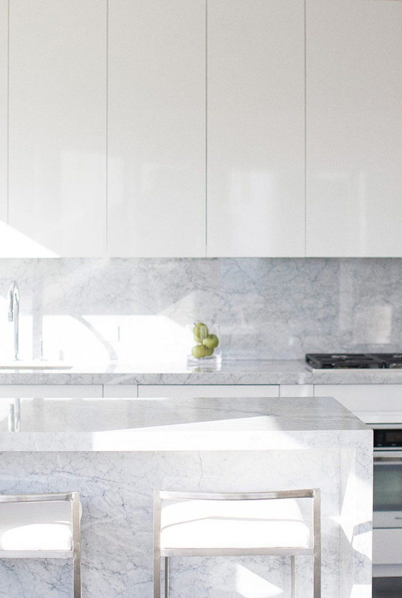 - White Clean Cabinets With Bianco Carrara Marble Counters And