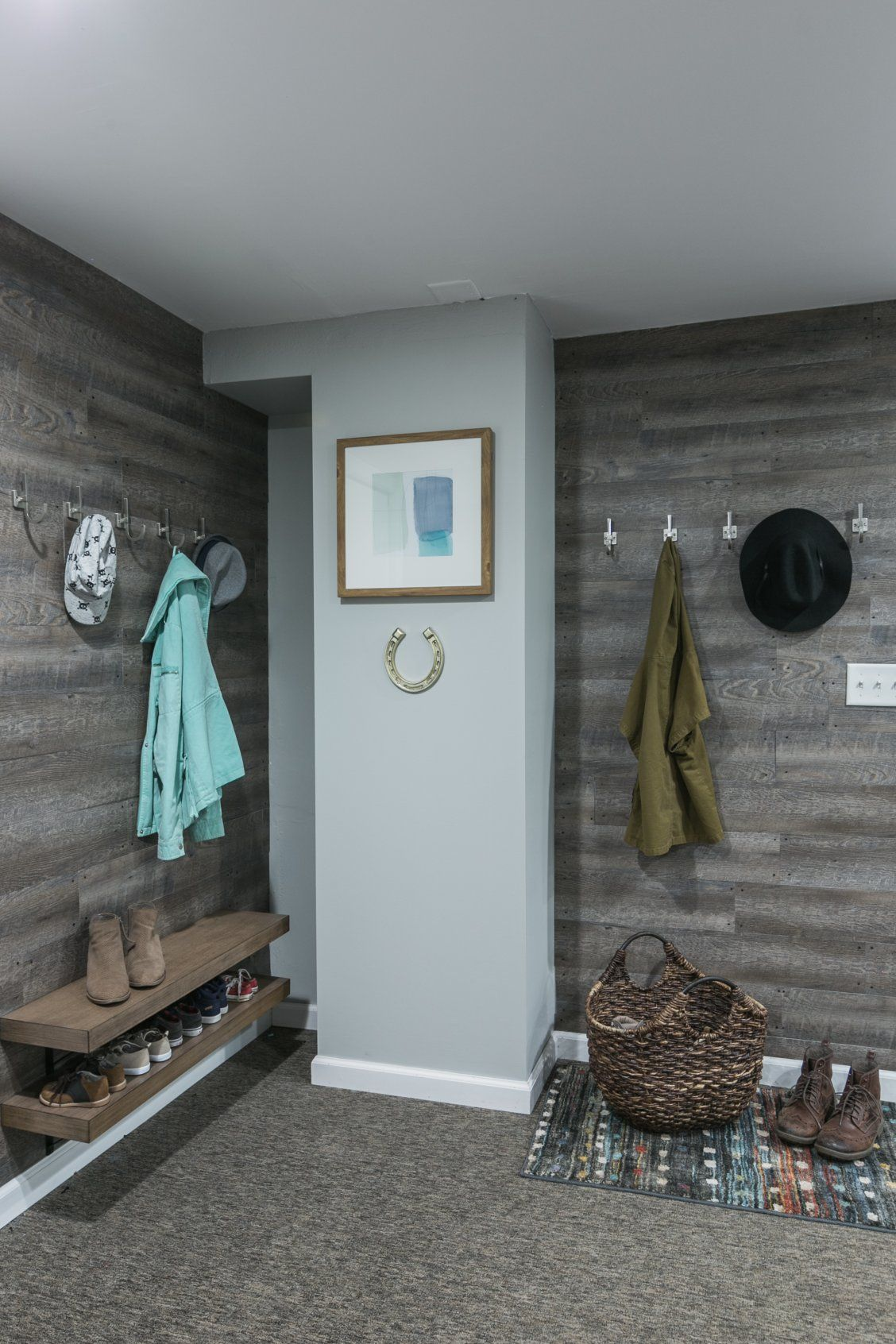 A basement mudroom gets an updated look with peel-and-stick flooring on the wall.