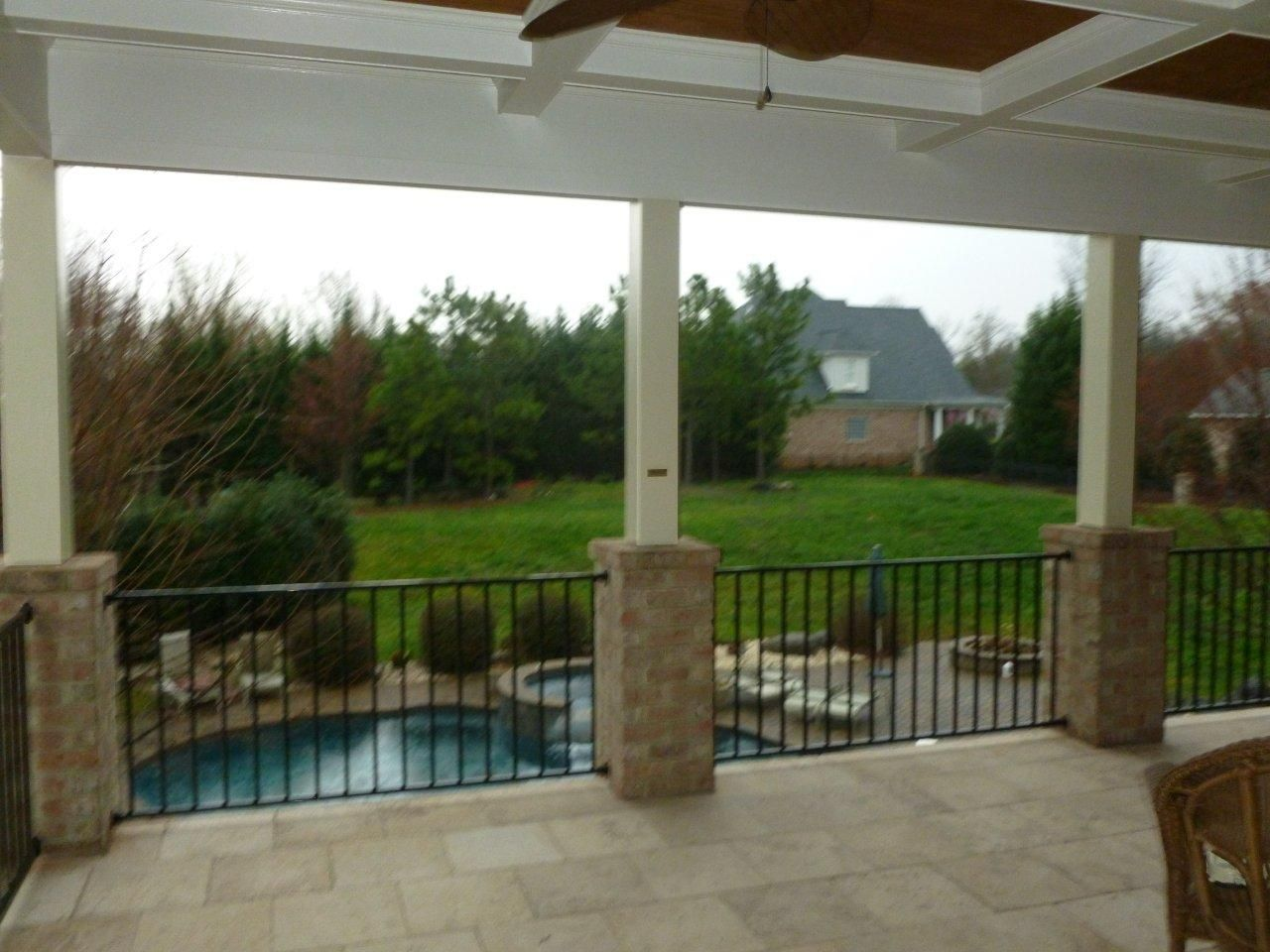 Open porch with brick columns and a travertine stone floor for Patio pillars