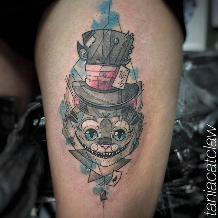 Sketchy Chesire Cat tattoo on the left thigh.