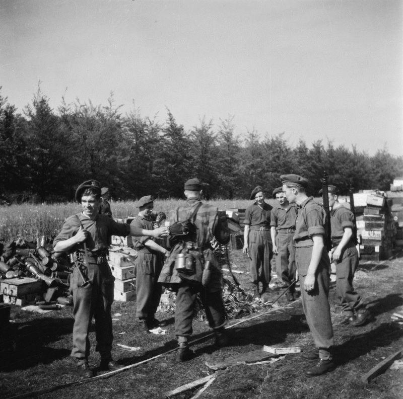Солдат 6-й немецкой парашютной дивизии бросает пулеметную ленту в поле у голландского городка Суст