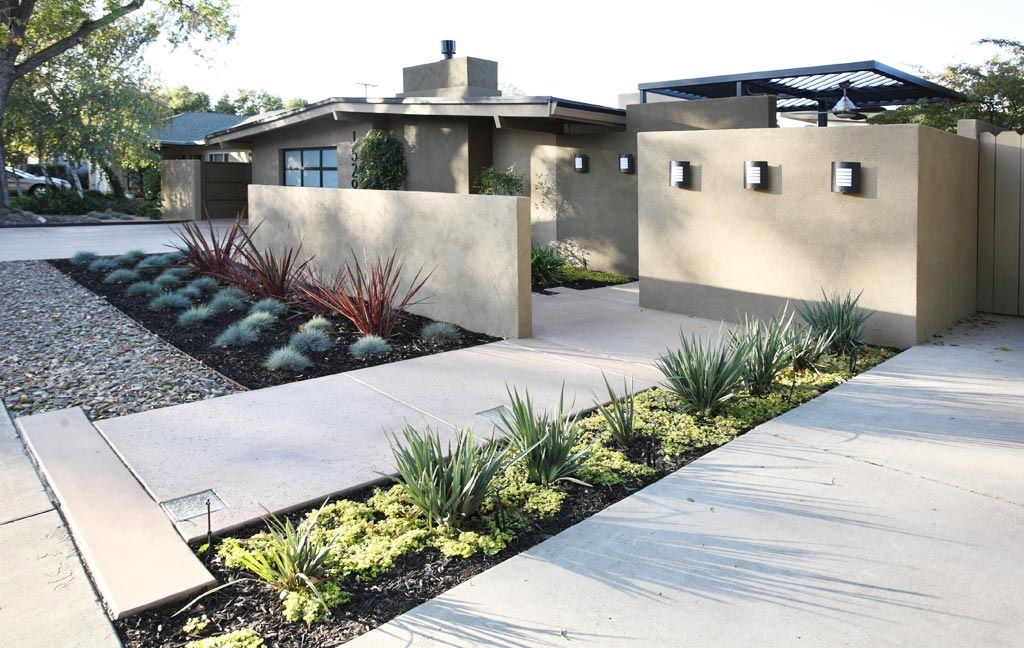 The low wall brings separation from the street and a sense Modern front yard landscaping