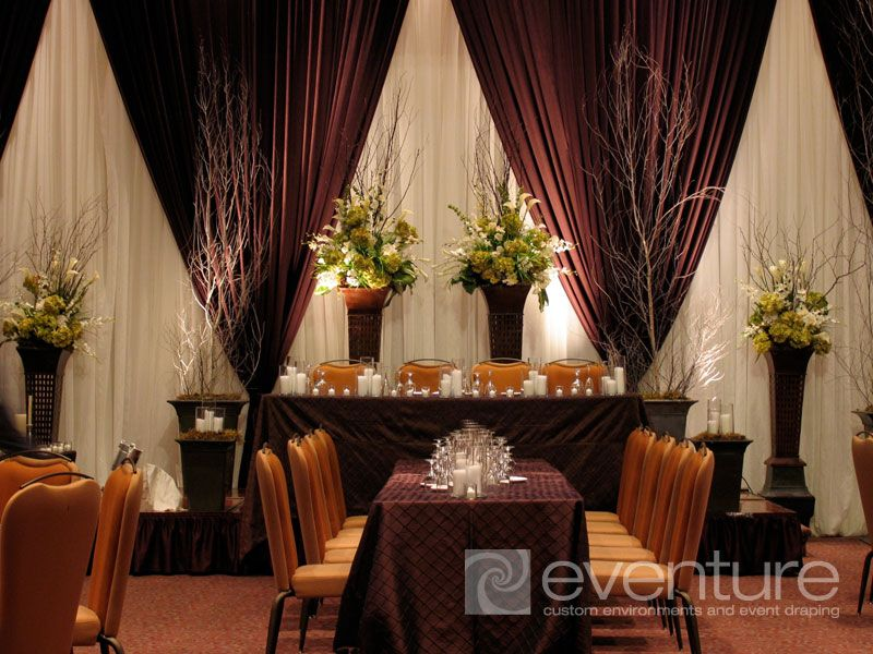 flower arrangements in front of draping