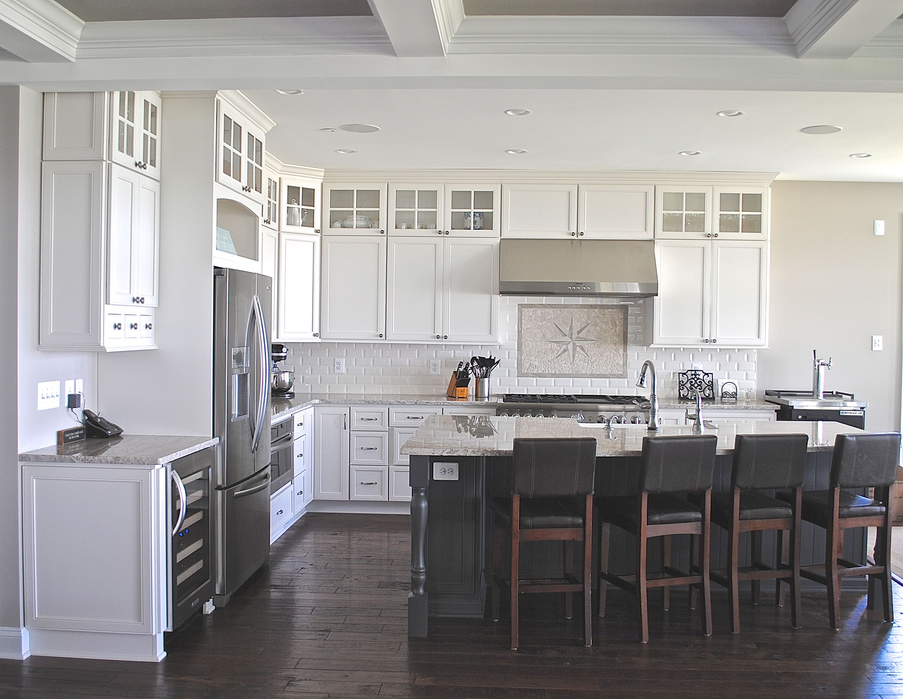 Coastal White Kitchen With Dark Grey Island Cabinets Stacked Cabinets With Glass Accents
