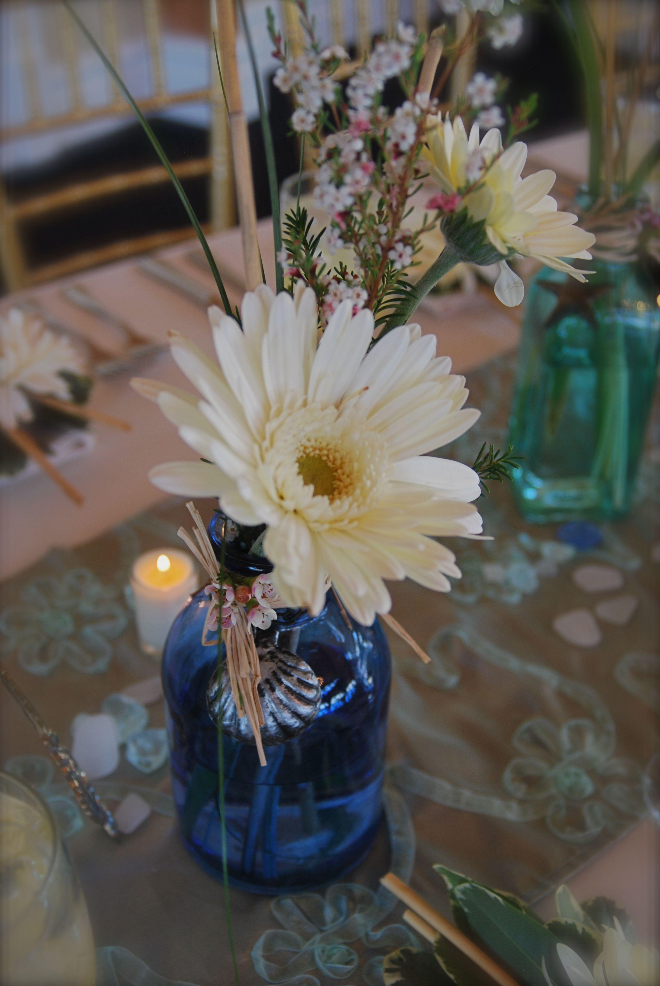 gerbera daisy in jar, vintage bottles centerpiece, bottles