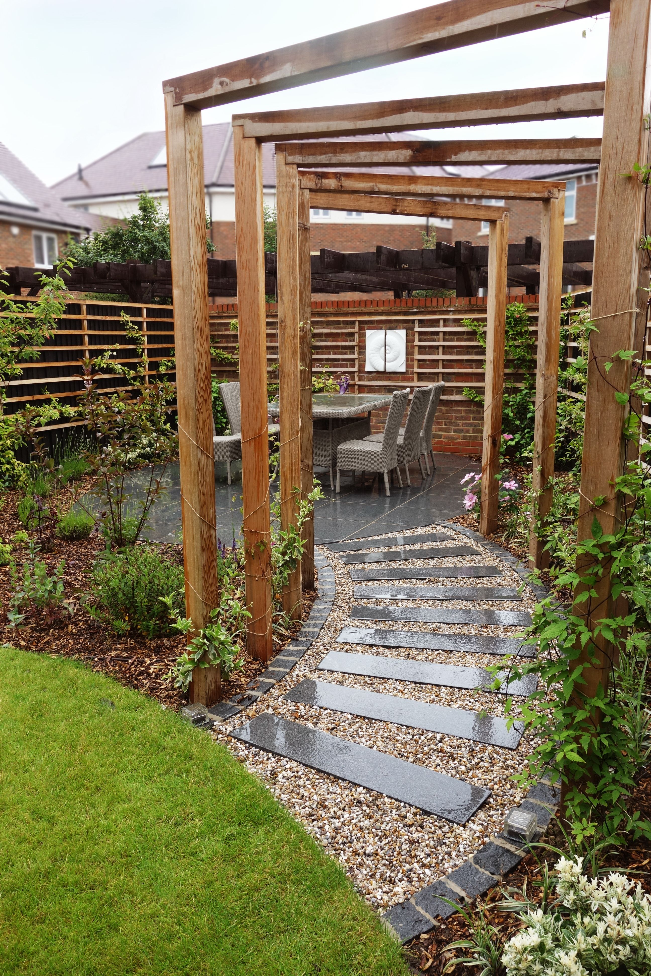 Photo of Stepping stones, a pergola, wall sculpture and interesting planting provide thes…