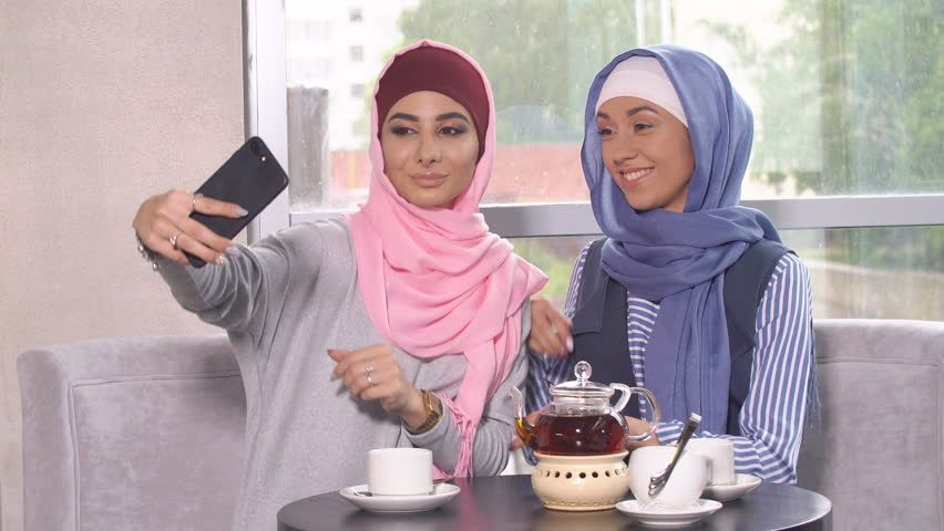 Ad: Two young women in hijabs do selfie on a smartphone. Muslim women in a cafe | Shutterstock Footage | Keywords: adult, app, arab, arabian, attire, attractive, beautiful, business, cheerful, clothes, clothing, communication, computer, culture, ethnic, ethnicity, female, friends, girls, group, happiness, happy, headscarf, hijab, holding, hoods, international, internet, islam, lifestyles, mobile, modern, multicultural, muslim, nationality, phone, portrait, religion, religious, smart, smartfone,  #businessattireforyoungwomen