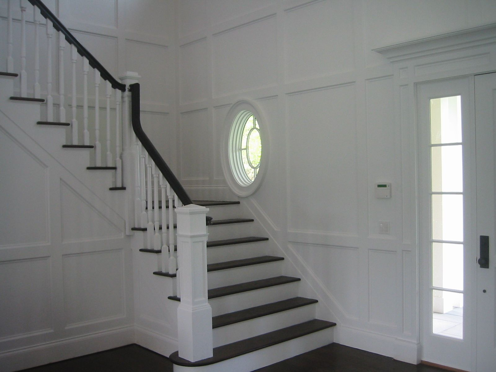 L shaped staircase with eliptical window at landing ...