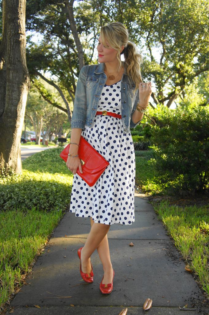 Black & white polka dot dress with denim jacket and red belt, shoes, and