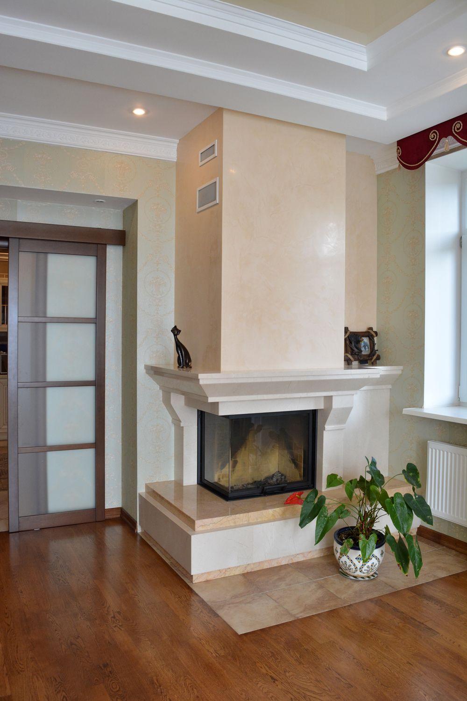 Камин в гостиной выполнен из мрамора в стиле легкого английского стиля.
