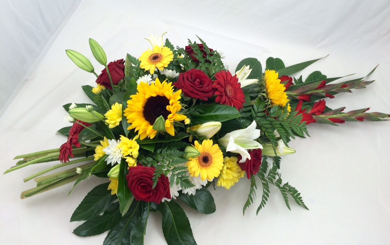 One of our vibrant teardrop shaped wreaths funeral flowers one of our vibrant teardrop shaped wreaths funeral flowers sunflower lily gerbera izmirmasajfo